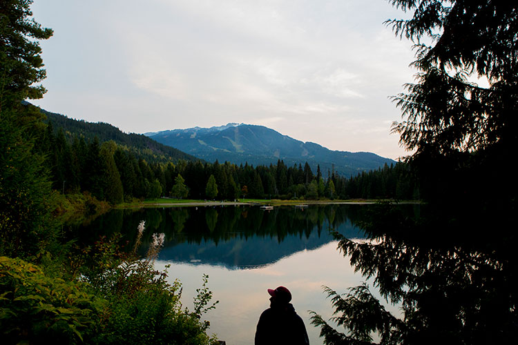 A man looks out over Lost Lake at the mountains in the background.