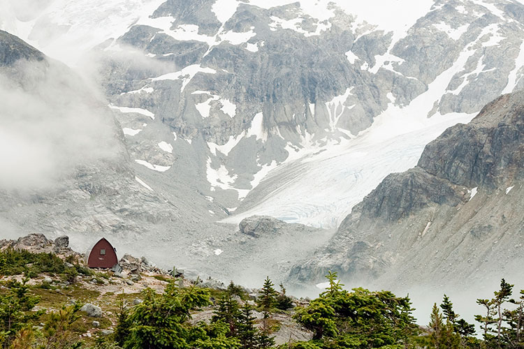 A rustic cabin sits amongst rocks and alpine shrubs at the top of the Wedgemount Lake trail in Whistler.