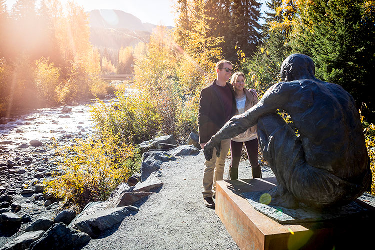 A couple look at public art in Whistler in the fall.