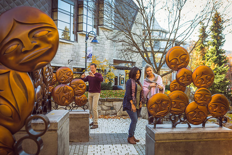 People admire the Timeless Circle sculpture in the beauty of fall in Whistler.