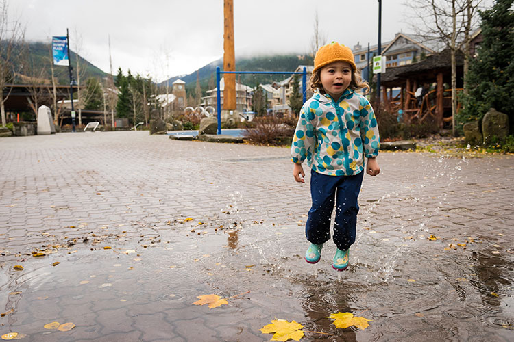 A child splashes in a puddle along Whistler's Village Stroll in the fall.