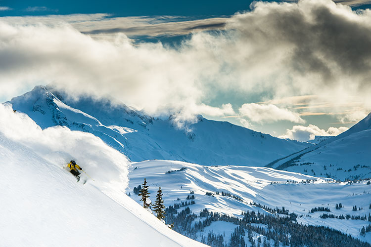 A skier sends it down a steep slope through powdery snow on Whistler Blackcomb.