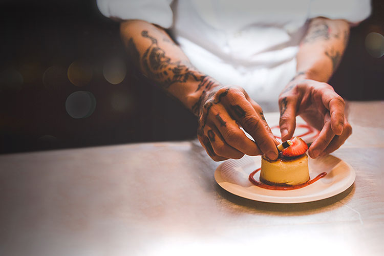 A chef's tattooed hands place the finishing touches on a dessert at Whistler's Cornucopia Festival.