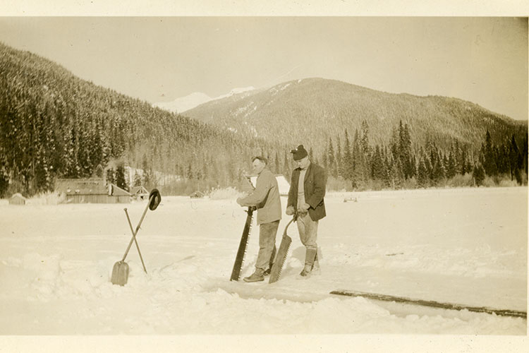 An archival photo of two men cutting ice on Alta Lake in 1917.