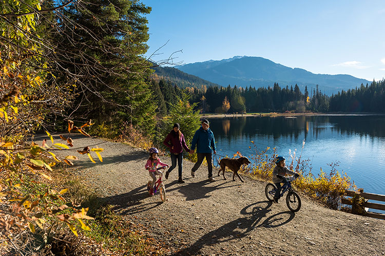 A family walk around Lost Lake in Whistler with their dog in the fall.