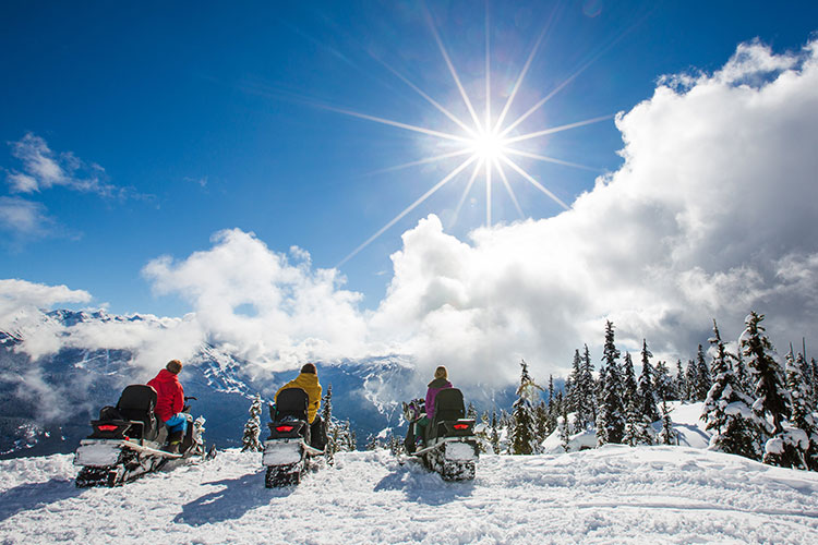 Three snowmobilers stop riding to take in the views on a sunny winter's day in Whistler's backcountry.