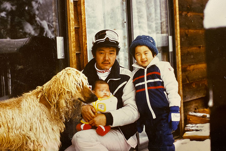 Toshi Hamazaki poses with his family, a baby girl sits on his knee while a toddler leans on his shoulder, the family dog is there too!