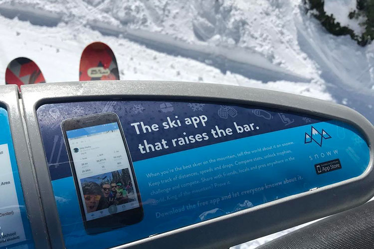 The ad for the Snoww app on a ski chair bar.