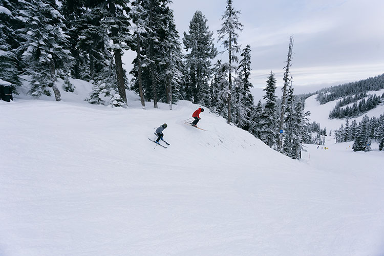 A father and son ski on Whistler Blackcomb on opening day.