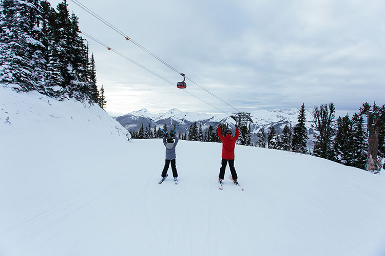 Father and son skiers raise their arms celebrating their first day on the slopes for this season.