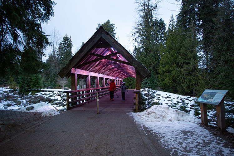 Two skiers walk across the covered bridge that connects the Village and Upper Village in Whistler.