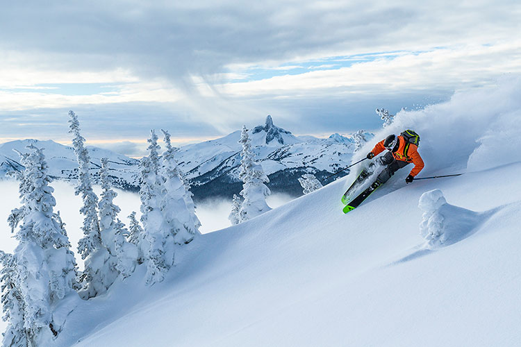 A skier showers powder as he skis down Whistler Blackcomb with Black Tusk in the background.