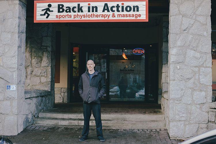 Mike Conway stands below his business sign, Back In Action, in Whistler.