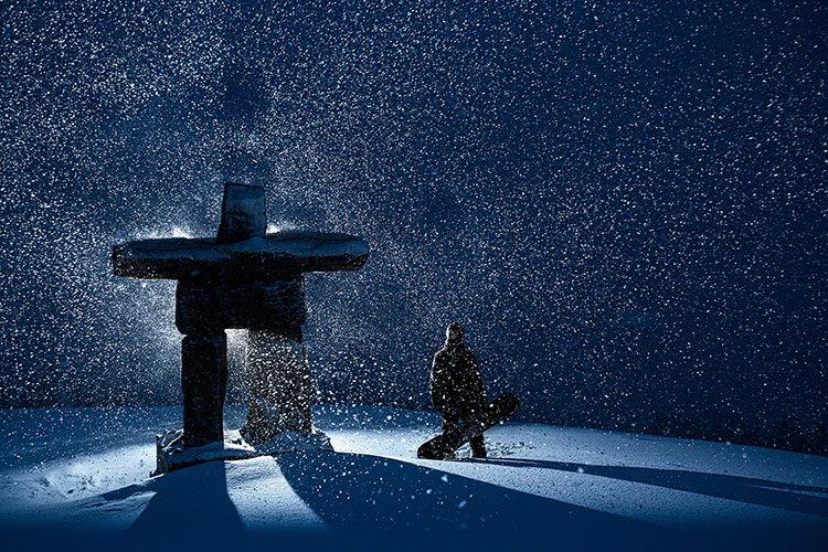 A snowboarder stands next to an inuksuk in Whistler while the snow flies.