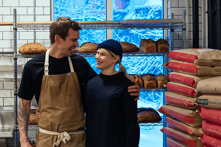 Ed and Natasha Tatton from Eds BrEd hug each other in front of a rack of sourdough.