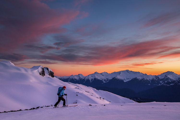 Skier going up the mountain against a sunset