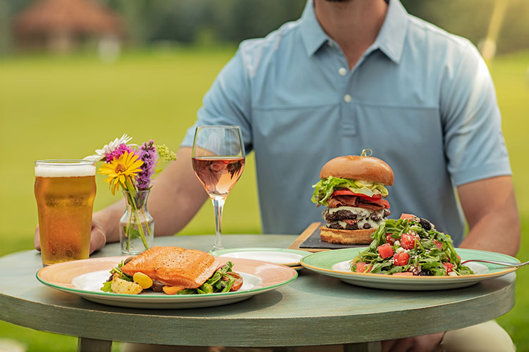 A summery table at the Fairmont Chateau Whistler Golf Course with salmon, salad and their famous Chip Out Burger.