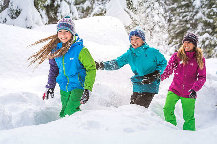 A family play in the deep snow in Whistler.