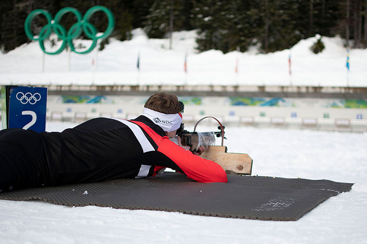 Instructor, Angus Tweedie lies prone on his belly, taking a shot at the target with his rifle during the biathlon experience at Whistler Olympic Park.