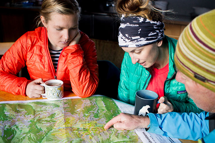 A group of three study a map to plan their trip into Whistler's backcountry.
