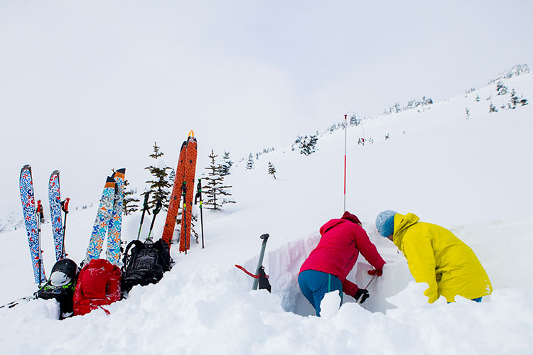 Two backcountry skiers dig a snow pit.