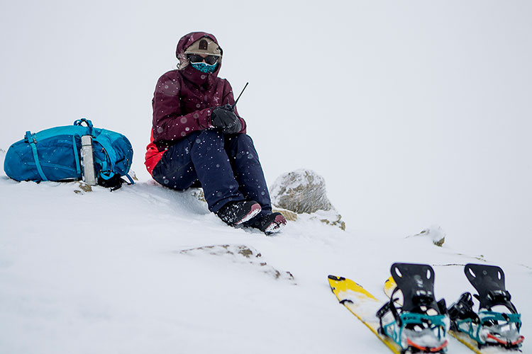 A snowshoer sits in the snow on a satellite phone in Whistler's backcountry.