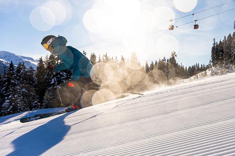 Skier on a groomed run in the sunshine in Whistler.