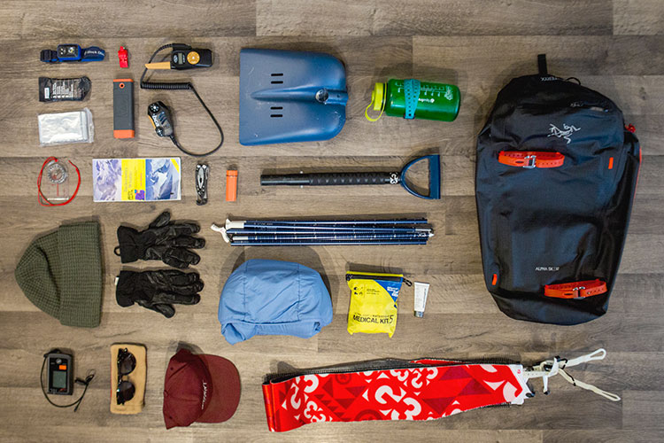 An aerial view of a backpack and it's contents, all things you need to venture into the backcountry in winter.