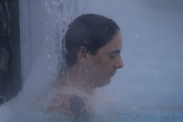 Court Larabee closes his eyes and relaxes under a warm waterfall at the Scandinave Spa Whistler.