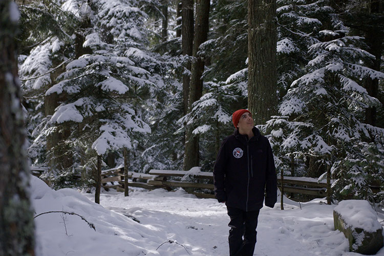 Court Larabee walks a snowy trail in the forests of Whistler.