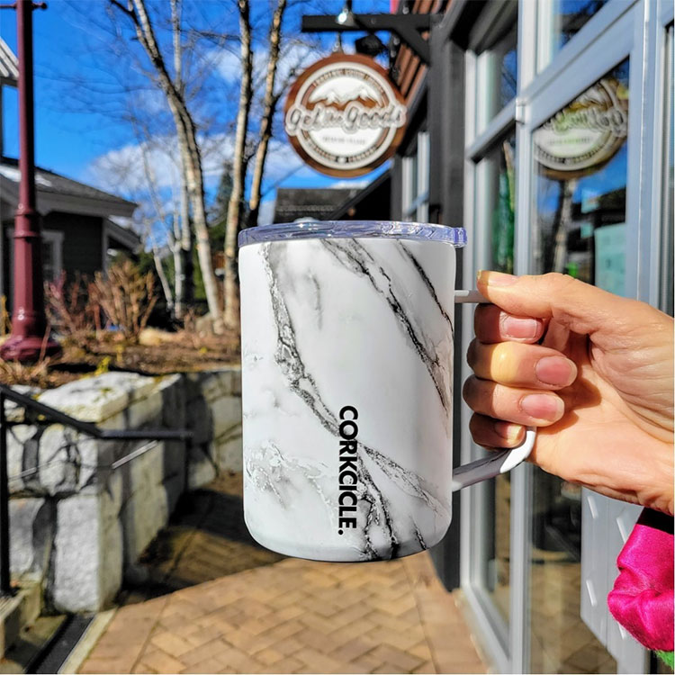 A woman holds a Corkcicle mug outside Get The Goods in Whistler.