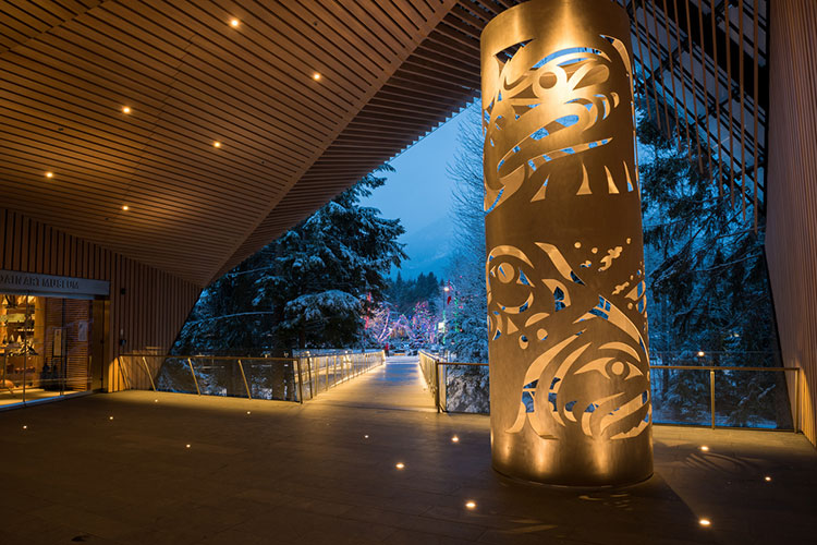 The entrance of the Audain Art Museum lit up in the evening.