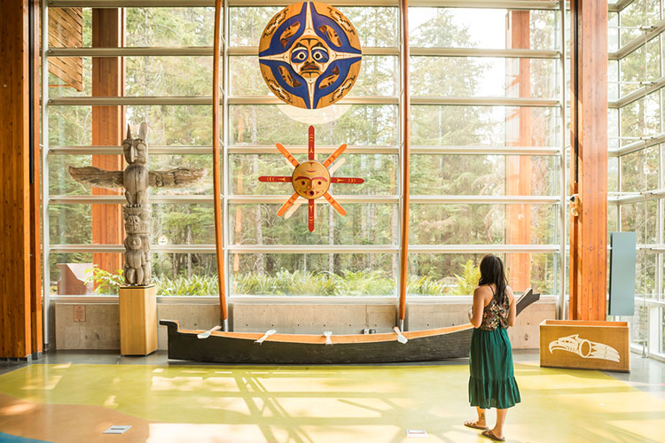 A woman looks up at artwork above a canoe at the Squamish Lil'wat Cultural Centre.