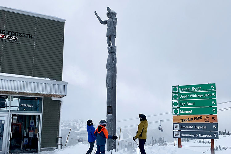 Three skiers look up at the welcome figure on Whistler Mountain.