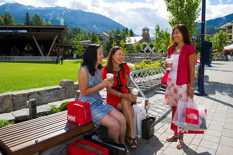 A group of three women stop for a coffee while shopping in Whistler in the summer.