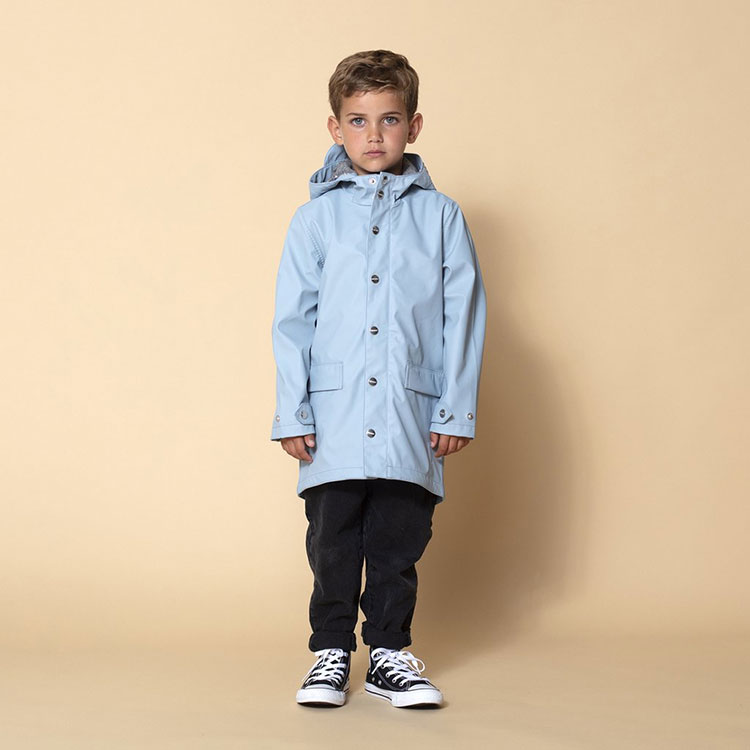 A young boy models the Lazy Geese rain jacket in blue.