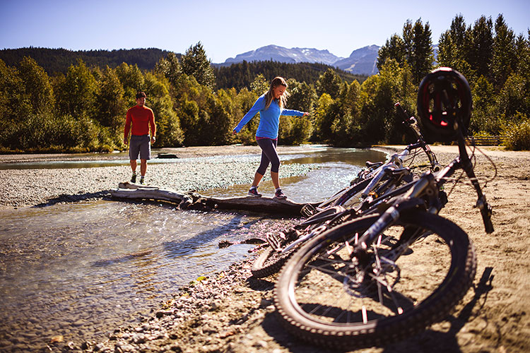A man and woman leave their bikes in the sand and walk over a fallen log to a bank in the river.