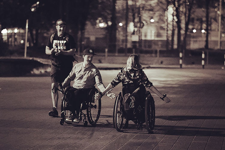 A man and woman in wheelchairs high five after completing the Wings for Life World Run.