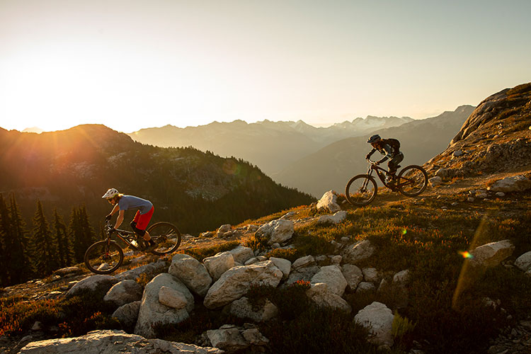 Two mountain bikers make their way down a trail in Whistler's high alpine as the sun begins to set.