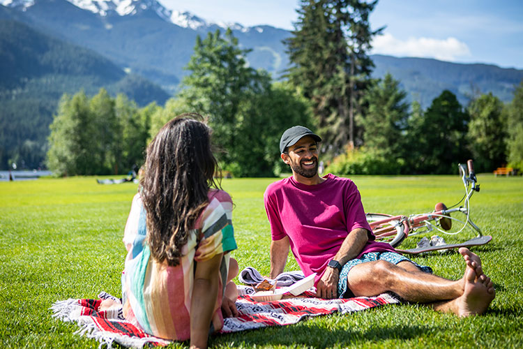 A couple hang out on the grassy lawn of a Whistler lake in summer.