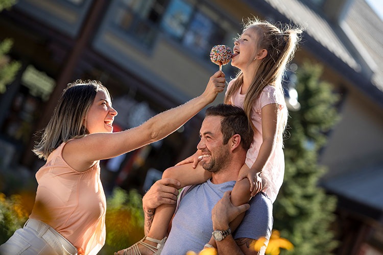 A girl sits on her father's shoulders as her mum feeds her a toffee apple in Whistler.