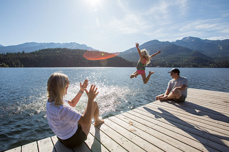 A child jumps into a lake in Whistler on a sunny day.