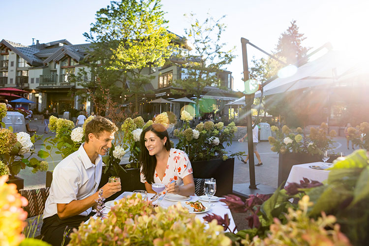 A couple dine on a sunny patio in Whistler Village.