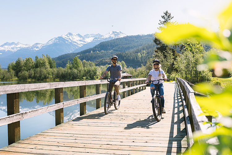A man and a woman bike along the Whistler Valley Trail boardwalk at Green Lake.