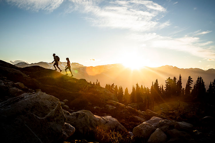 Two people hike on Whistler Blackcomb in the high alpine. The sun rises in the background.