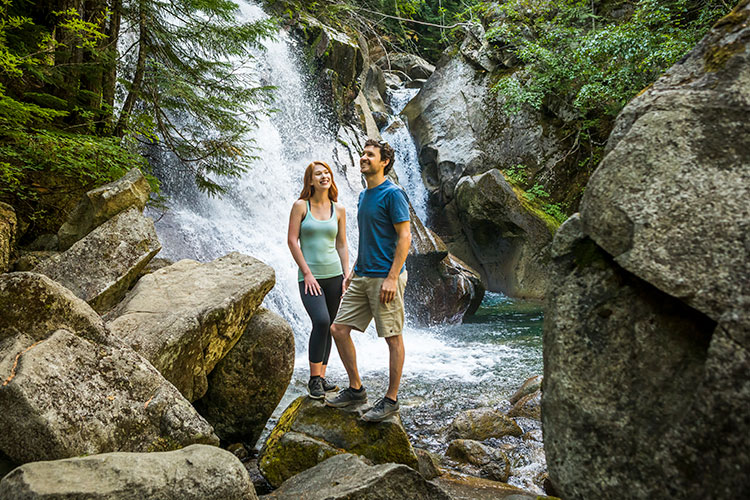 A couple stand at the base of Rainbow Falls in Whistler.