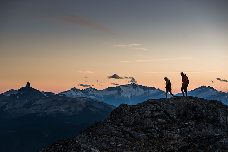 A couple hike high in the Coast Mountains with Black Tusk in the background as the sun sets in Whistler.