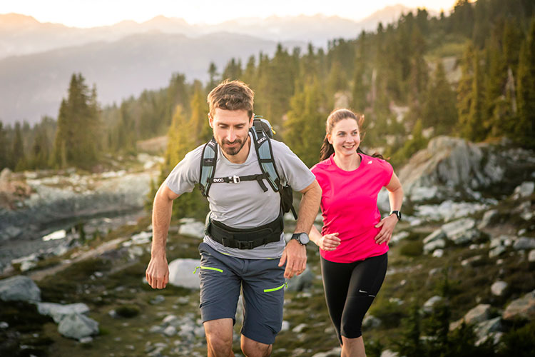 A man and woman trail run in the high alpine in Whistler.