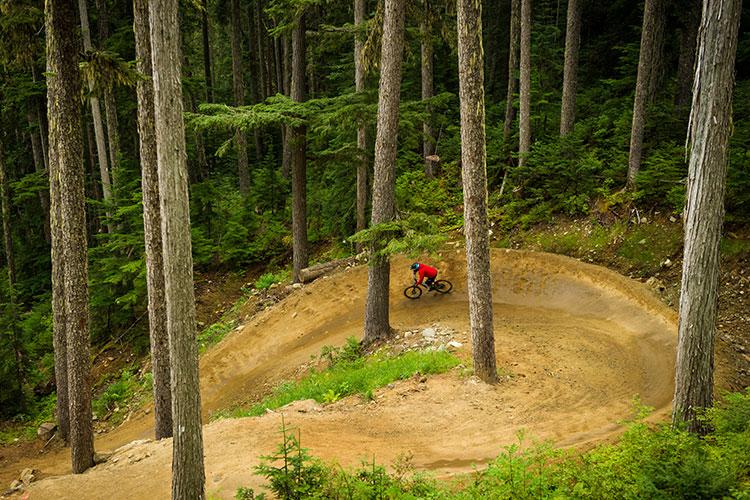 A mountain biker rides some big berms in Whistler Bike Park.