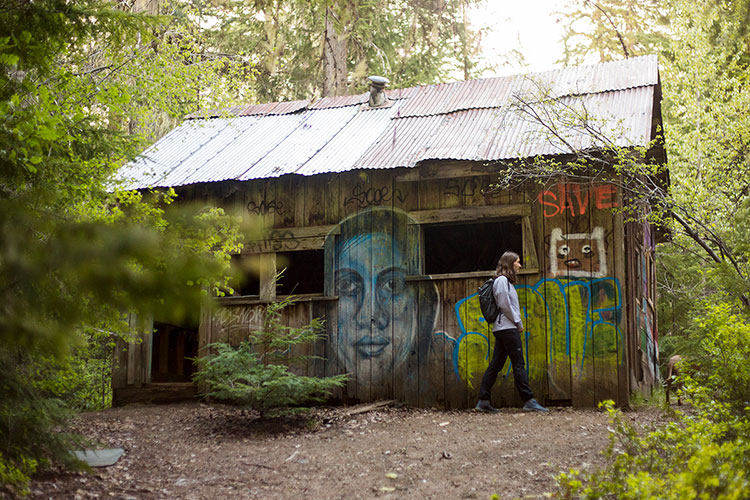 A woman looks at the graffiti on the sides of an old cabin at the Parkhurst site in Whistler.
